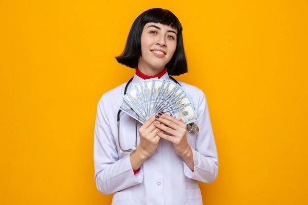 Glimlachend jong mooi kaukasisch meisje in doktersuniform met stethoscoop die geld aanhoudt