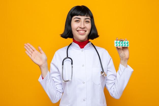 Glimlachend jong, mooi kaukasisch meisje in doktersuniform met stethoscoop die pilverpakking vasthoudt en hand open houdt