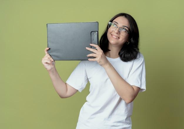 Glimlachend jong, mooi kaukasisch meisje met een bril die omhoog kijkt en klembord vasthoudt op olijfgroene ruimte