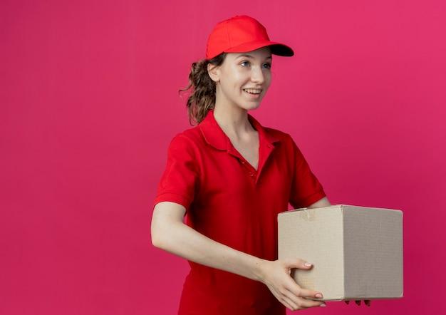 Glimlachend jong mooi leveringsmeisje die rood uniform en pet dragen die recht op zoek houden kartonnen doos geïsoleerd op karmozijnrode achtergrond met kopie ruimte