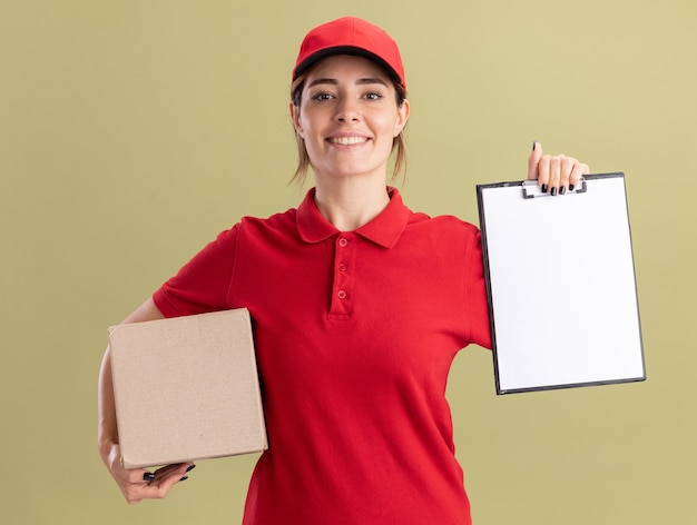 Glimlachend jong mooi leveringsmeisje in eenvormig holdingsklembord en kartondoos op groen olijf