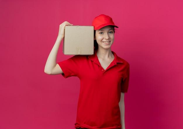 Glimlachend jong mooi leveringsmeisje in rood uniform en glb die kartondoos op schouder houden die op karmozijnrode achtergrond met exemplaarruimte wordt geïsoleerd
