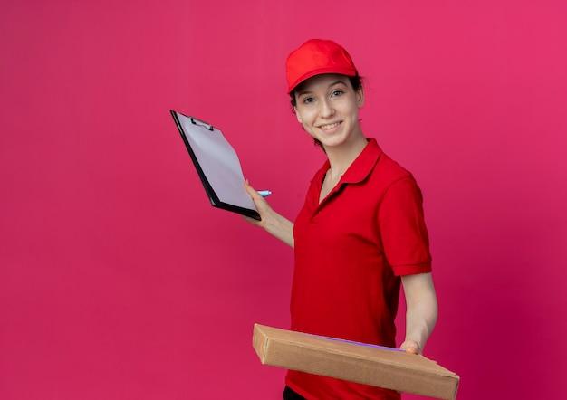 Glimlachend jong mooi leveringsmeisje in rood uniform en glb die pizzapakket en klembord met pen houden die op karmozijnrode achtergrond met exemplaarruimte wordt geïsoleerd