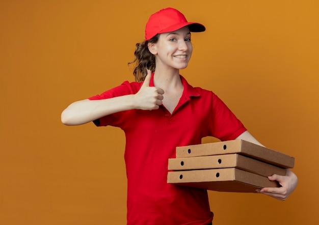 Glimlachend jong mooi leveringsmeisje in rood uniform en glb die pizzapakketten houden en duim tonen die omhoog op oranje achtergrond wordt geïsoleerd