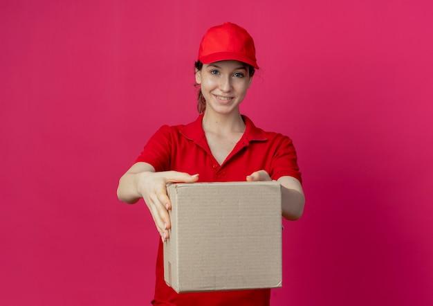 Glimlachend jong mooi leveringsmeisje in rood uniform en glb die zich uit kartondoos uitstrekken bij camera die op karmozijnrode achtergrond met exemplaarruimte wordt geïsoleerd