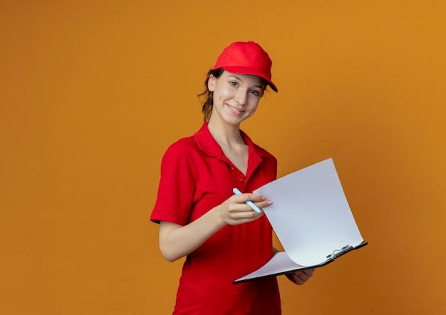 Glimlachend jong mooi leveringsmeisje in rood uniform en glb-holdingsklembord en pen die op oranje achtergrond met exemplaarruimte wordt geïsoleerd