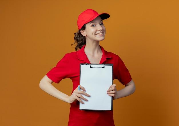 Glimlachend jong mooi leveringsmeisje in rood uniform en glb-holdingspen en klembord tonen bij camera die op oranje achtergrond met exemplaarruimte wordt geïsoleerd