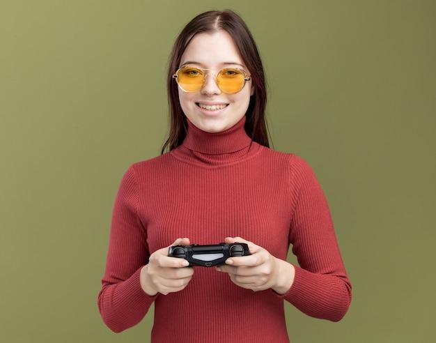 Glimlachend jong mooi meisje dat een zonnebril draagt die de joystick van de spelbesturing vasthoudt om een spel te spelen