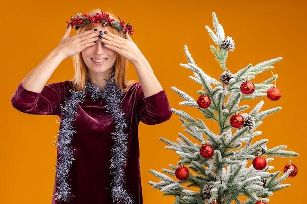 Glimlachend jong mooi meisje dat in de buurt van de kerstboom staat en een rode jurk en een krans draagt met een slinger op de nek bedekte ogen met handen geïsoleerd op een oranje muur