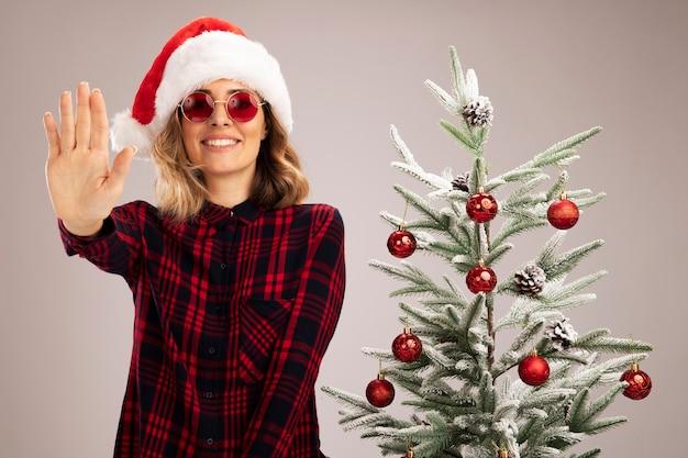 Glimlachend jong mooi meisje dat in de buurt van een kerstboom staat en een kerstmuts draagt met een bril die de hand uitsteekt naar de camera die op een witte achtergrond wordt geïsoleerd
