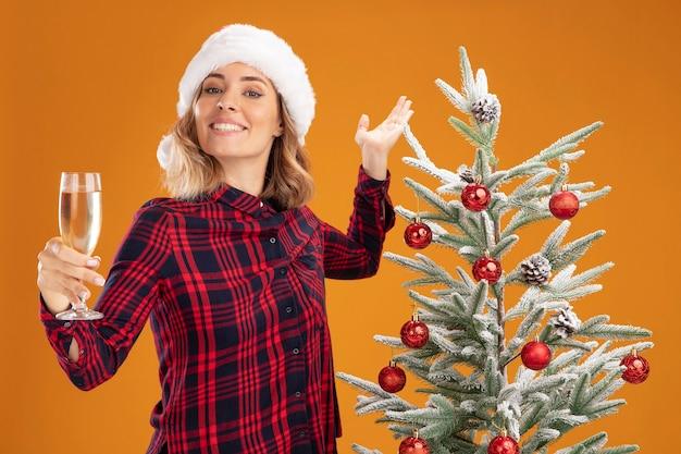 Glimlachend jong mooi meisje dat in de buurt van een kerstboom staat met een kerstmuts die een glas champagne uithoudt naar de camera die de hand spreidt die op een oranje achtergrond wordt geïsoleerd