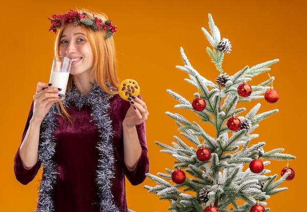 Glimlachend jong mooi meisje dat in de buurt van een kerstboom staat met een rode jurk en een krans met een slinger op de nek die koekjes vasthoudt en melk drinkt die op een oranje muur is geïsoleerd