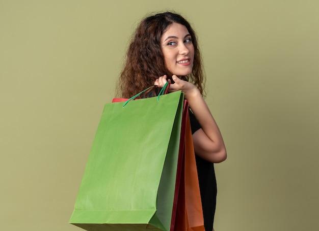 Glimlachend jong mooi meisje dat in profielweergave staat met boodschappentassen op de schouder en kijkt achter geïsoleerd op olijfgroene muur met kopieerruimte