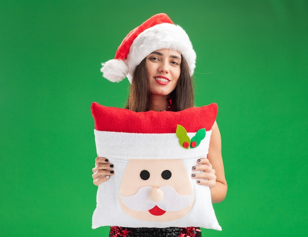 Glimlachend jong mooi meisje dat kerstmishoed met slinger op hals draagt die kerstmishoofdkussen standhoudt dat op groene muur wordt geïsoleerd