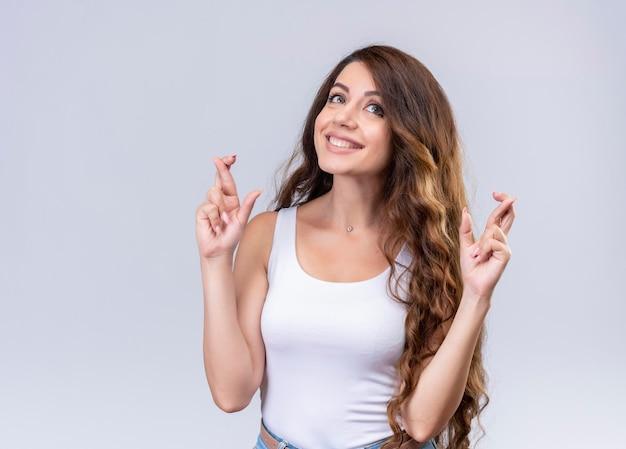 Glimlachend jong mooi meisje dat omhoog kijkt en gekruiste vingersgebaar met exemplaarruimte doet