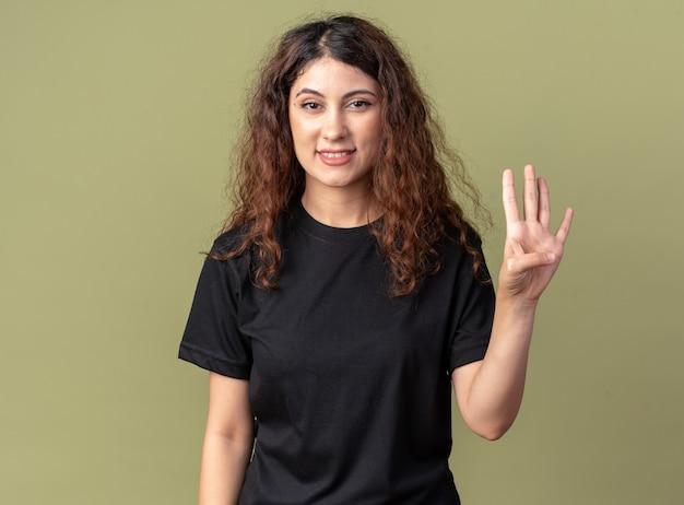 Glimlachend jong mooi meisje dat vier met hand toont