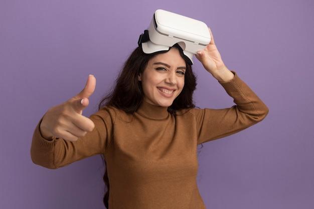 Glimlachend jong mooi meisje dat vr-headsetpunten draagt en vasthoudt aan de voorkant die op paarse muur worden geïsoleerd