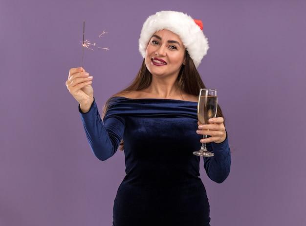 Glimlachend jong mooi meisje die blauwe jurk en kerstmuts dragen die wonderkaarsen houden en glas champagne stak op camera geïsoleerd op paarse achtergrond