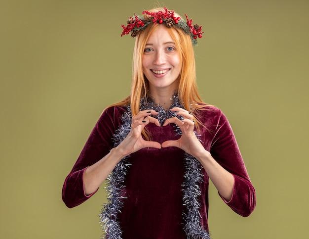 Glimlachend jong mooi meisje draagt rode jurk met krans en garland op nek met hart gebaar geïsoleerd op olijfgroene achtergrond