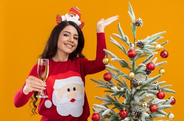Glimlachend jong mooi meisje dragen hoofdband van de kerstman en trui permanent in de buurt van versierde kerstboom met glas champagne kijken camera wijzend op boom geïsoleerd op een oranje achtergrond