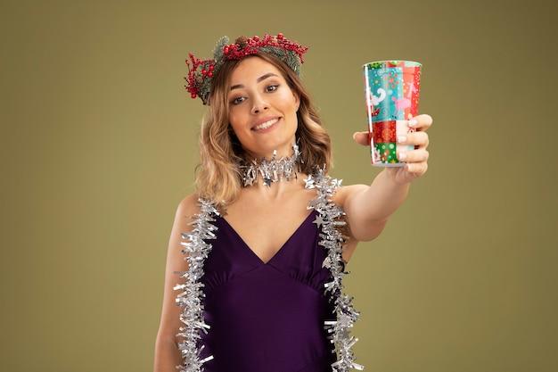 Glimlachend jong mooi meisje, gekleed in paarse jurk en krans met guirlande op nek die kerstbeker uithoudt op camera geïsoleerd op olijfgroene achtergrond