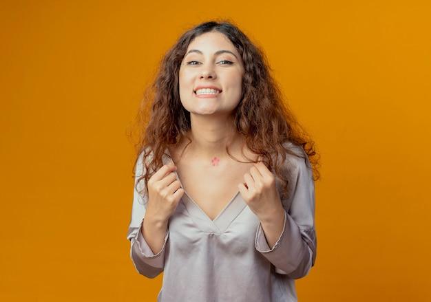Glimlachend jong mooi meisje greep kraag geïsoleerd op geel