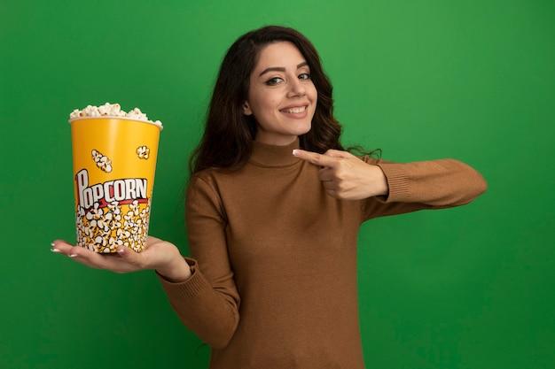 Glimlachend jong mooi meisje houdt en wijst naar emmer popcorn geïsoleerd op groene muur green