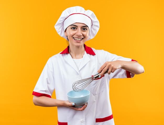 Glimlachend jong mooi meisje in chef-kok uniform bedrijf kom met garde geïsoleerd op oranje muur