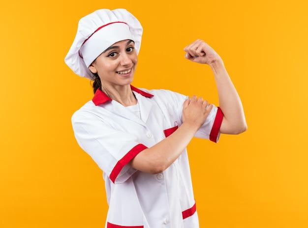 Glimlachend jong mooi meisje in chef-kok uniform doen sterk gebaar