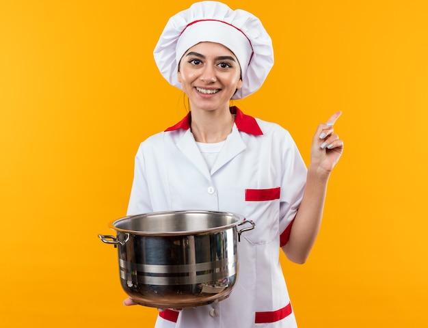Glimlachend jong mooi meisje in chef-kok uniform houden en kijken naar steelpan punten aan de zijkant