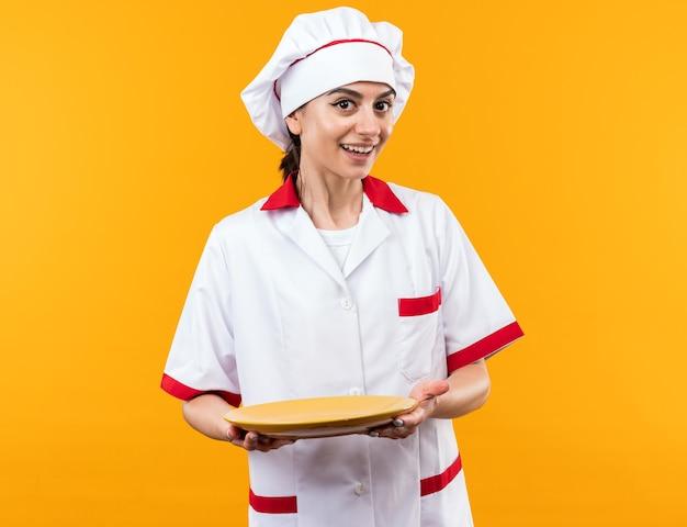 Glimlachend jong mooi meisje in chef-kok uniform met bord