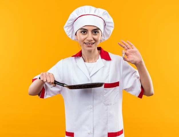 Glimlachend jong mooi meisje in chef-kok uniform met koekenpan met goed gebaar geïsoleerd op oranje muur