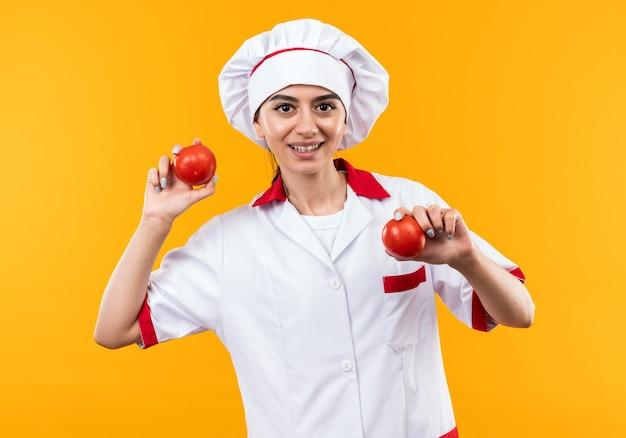 Glimlachend jong mooi meisje in chef-kok uniform met tomaten geïsoleerd op oranje muur