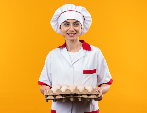Glimlachend jong mooi meisje in uniform van de chef-kok met partij eieren geïsoleerd op oranje muur