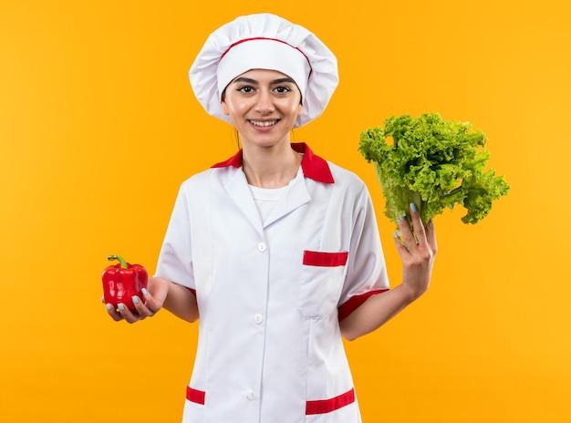 Glimlachend jong mooi meisje in uniform van de chef-kok met peper met salade geïsoleerd op oranje muur
