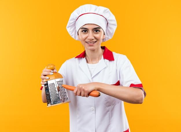Glimlachend jong mooi meisje in uniform van de chef-kok met rasp met wortel geïsoleerd op oranje muur