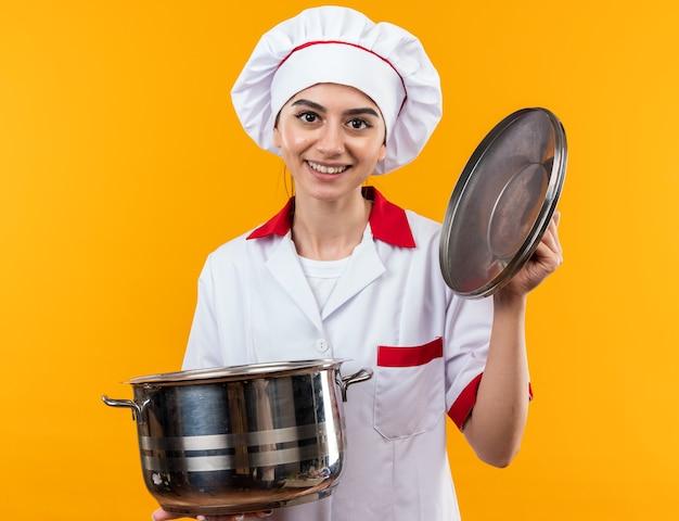 Glimlachend jong mooi meisje in uniform van de chef-kok met steelpan met deksel geïsoleerd op oranje muur