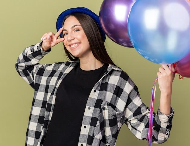 Glimlachend jong mooi meisje met blauwe hoed met ballonnen die vredesgebaar tonen