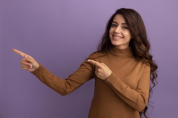 Glimlachend jong mooi meisje met bruine coltrui wijst aan de zijkant geïsoleerd op een paarse muur met kopieerruimte