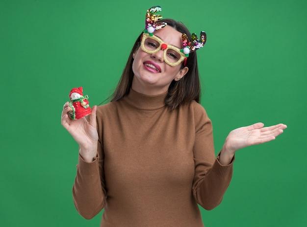 Glimlachend jong mooi meisje met bruine trui en kerstbril met kerstspeelgoed verspreidende hand geïsoleerd op groene muur green