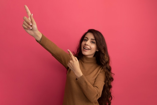 Glimlachend jong mooi meisje met coltrui wijst naar kant geïsoleerd op roze muur