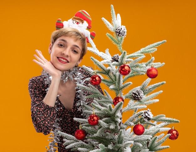 Glimlachend jong mooi meisje met de hoofdband van de kerstman en een klatergoudslinger om de nek die achter een versierde kerstboom staat en de hand onder de kin houdt geïsoleerd op een oranje muur