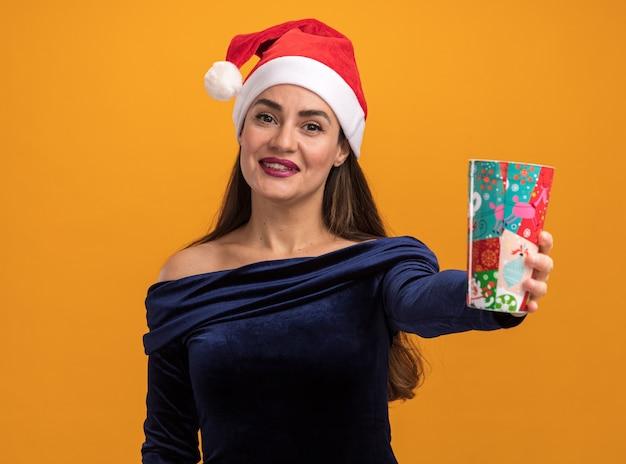 Glimlachend jong mooi meisje met een blauwe jurk en een kerstmuts die een kerstbeker uithoudt die op een oranje muur is geïsoleerd