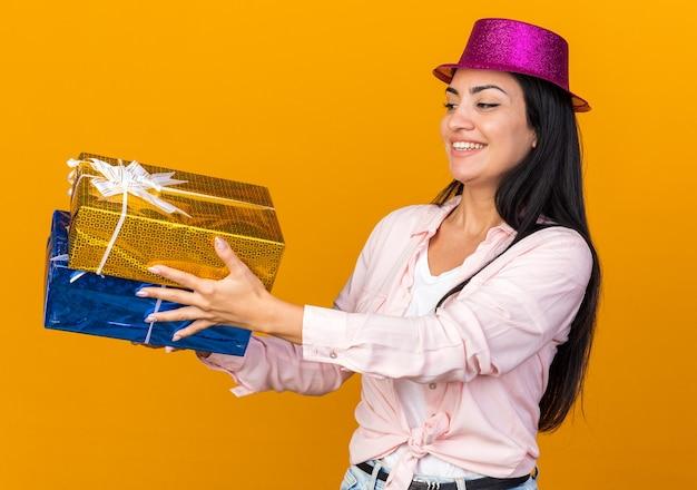 Glimlachend jong mooi meisje met een feesthoed die geschenkdozen aan de zijkant op een oranje muur vasthoudt