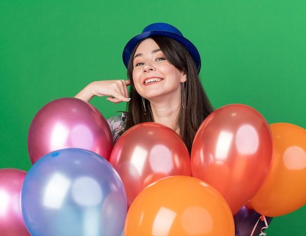 Glimlachend jong mooi meisje met een feestmuts die achter ballonnen staat en een telefoongebaar toont dat op een groene muur is geïsoleerd