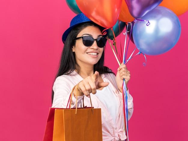 Glimlachend jong mooi meisje met een feestmuts met ballonnen en cadeauzakjes die je een gebaar laten zien