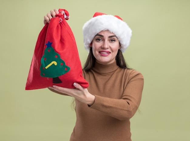 Glimlachend jong mooi meisje met een kerstmuts die een kerstzak uitsteekt die op een olijfgroene muur is geïsoleerd