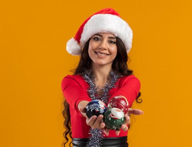 Glimlachend jong mooi meisje met een kerstmuts en een klatergoudslinger om de nek die zich uitstrekt over kerstballen geïsoleerd op een oranje muur met kopieerruimte