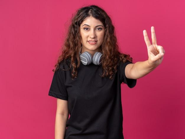 Glimlachend jong mooi meisje met een koptelefoon op de nek die vredesteken doet