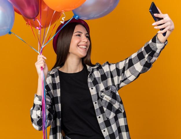 Glimlachend jong mooi meisje met feestmuts die ballonnen vasthoudt en een selfie neemt geïsoleerd op een oranje muur